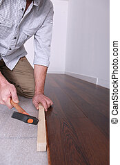 Man laying wooden flooring