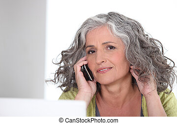 Attractive older woman with a phone