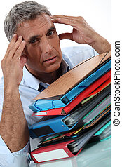 Man with stacks of paperwork