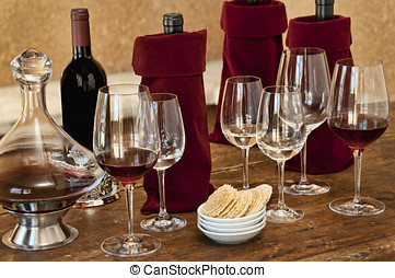 Wine tasting with bottles, glasses, crackers, on old wooden...