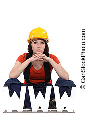 Female builder sat by letters