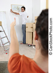 Couple hanging a picture frame