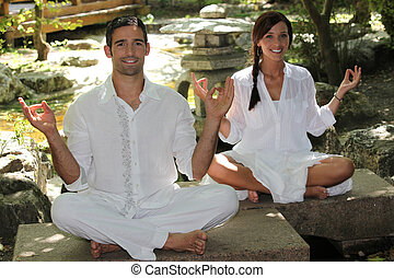 Couple meditating in garden