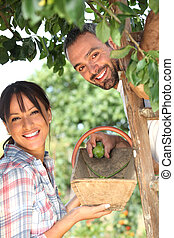 couple with ladder by tree
