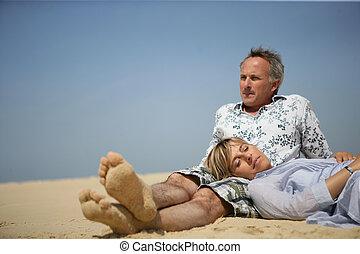 Married couple sat on a beach