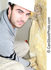 Man pushing wall insulation into place