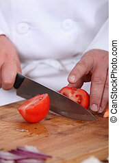 Chef chopping tomato