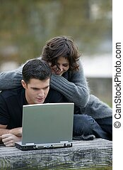 Couple using a laptop in the park