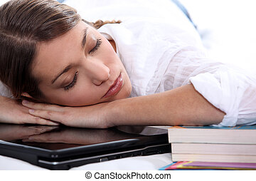 young woman sleeping on her computer