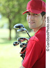 Golfer holding golf clubs smiling