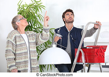 Man fixing ceiling light for old woman