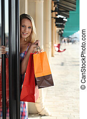blonde woman entering in a store