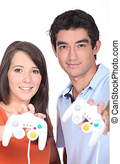 Couple stood holding video game control pads