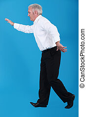 Senior businessman walking along invisible tight-rope