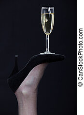 A champagne glass balanced on the sole of a shoe
