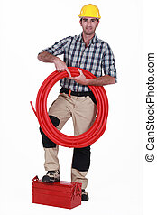 Tradesman holding corrugated tubing and propping his foot on...