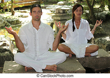 Couple meditating in stone garden