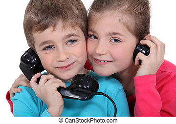 Brother and sister with old fashioned telephone