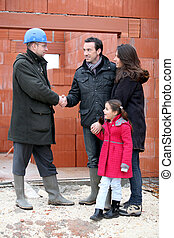 Young family visiting property developer