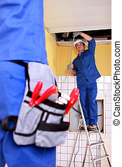 Two electrician repairing ceiling electrics