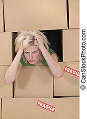 Stress blond woman amongst boxes