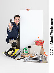 craftsman holding an ad board and a cell