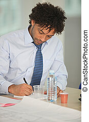Portrait of a businessman writing in a notepad