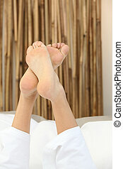 Shot of feet crossed on a bed
