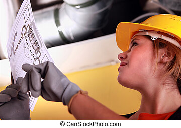 Female electrician with a wiring plan