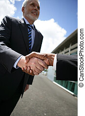 mature businessman all smiles shaking hands with male...