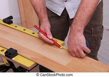 carpenter taking measurements to lay parquet