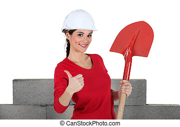 A female mason with a shovel