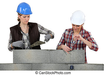 Two female mason working on a wall.