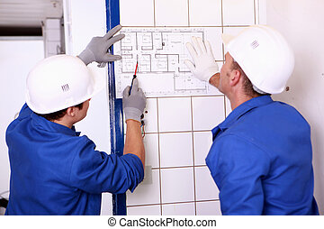 Two electricians inspecting electrical plan