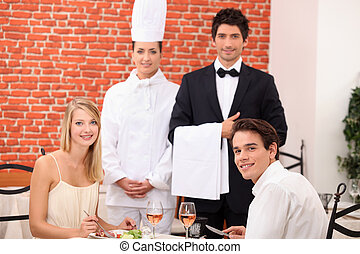 Restaurant staff stood with customers