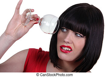 Woman checking empty wine glass