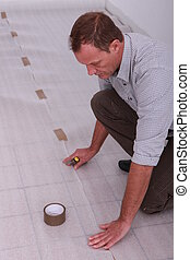 Man protecting floor with ground sheet