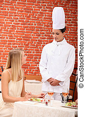 A chef talking with a patron