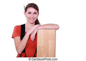 Female carpenter with laminate flooring