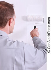 Man painting a wall white with a roller