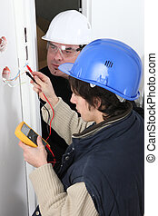 Worker using a multimeter