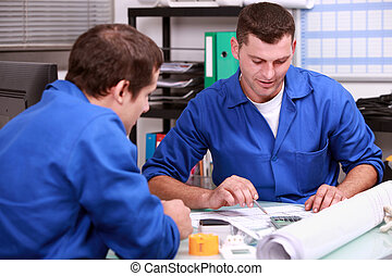 Skilled tradesmen examining a blueprint