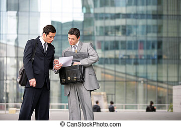 Two businessmen checking a document