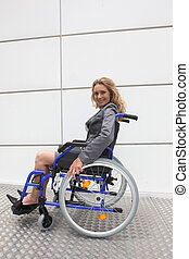 Smiling businesswoman in a wheelchair on a ramp