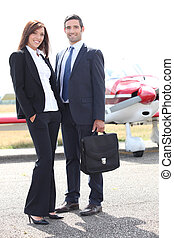 Business couple standing in front of a light aircraft