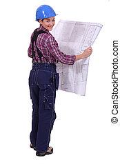 female construction worker watching a blueprint