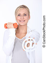 Young woman with a dumbbell and an internet @ sign