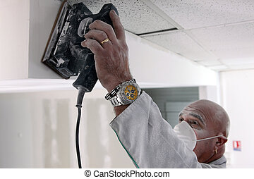 Man sanding plasterboard
