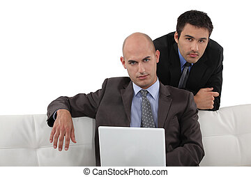 Smart executives sitting with a laptop