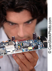 Man looking at  an electronic board